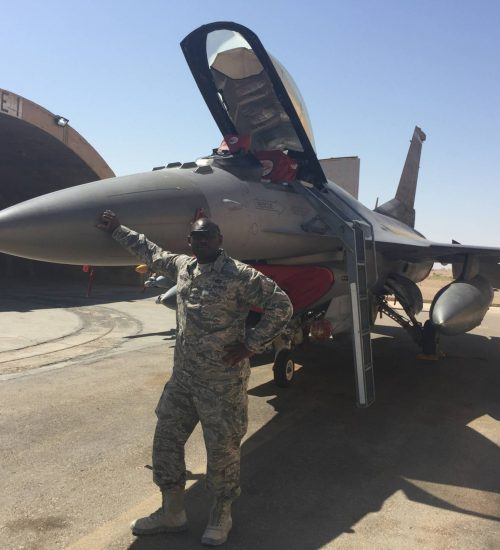 Man posing in front of fighter jet
