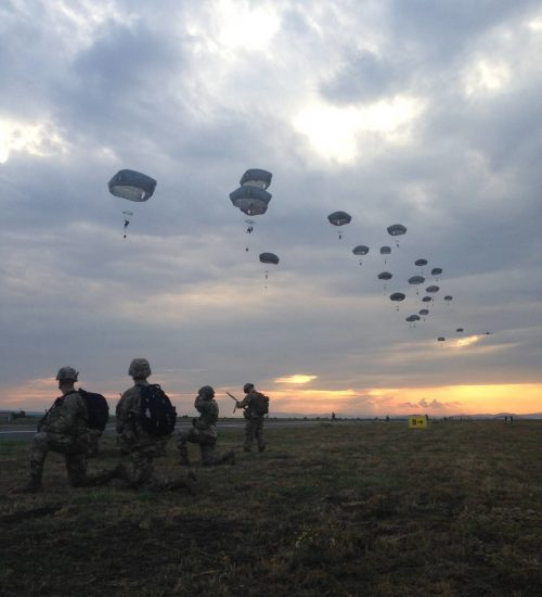 Airborne infantry parachuting onto an airfield