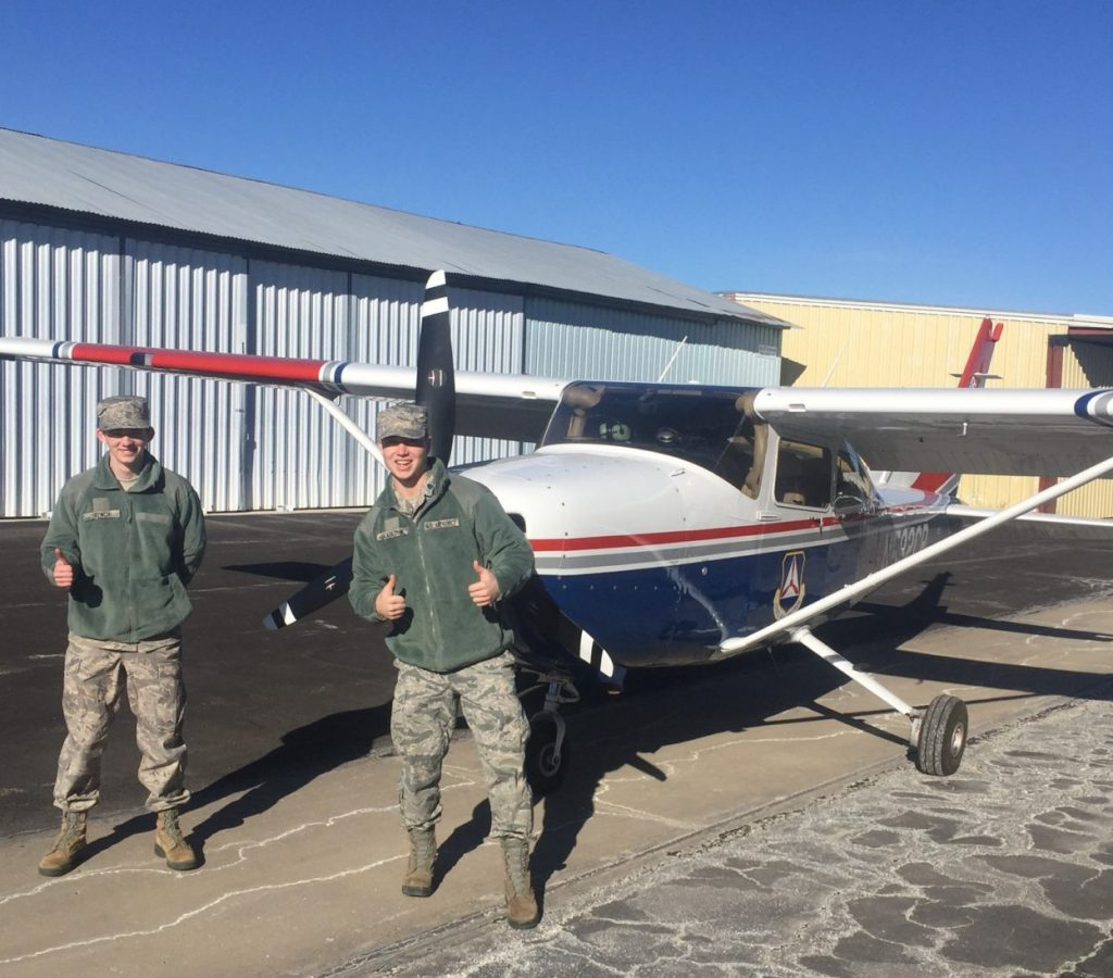 Two cadets standing in front of a civilian aircraft before a flight